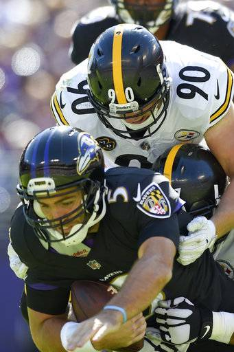 Baltimore Ravens quarterback Joe Flacco (5) is sacked by Pittsburgh Steelers outside linebacker T.J. Watt (90) and defensive end Stephon Tuitt (91) during the first half of an NFL football game in Baltimore, Sunday, Oct. 1, 2017.