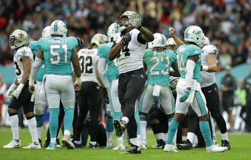 New Orleans Saints defensive end Cameron Jordan, center, reacts after sacking Miami Dolphins quarterback Jay Cutler during the second half of an NFL football game at Wembley Stadium in London, Sunday Oct. 1, 2017.