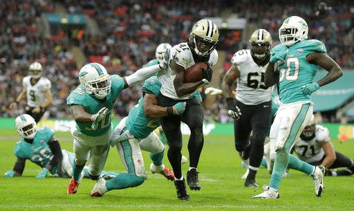 New Orleans Saints running back Alvin Kamara (41) runs past Miami Dolphins defenders to score a touchdown during the second half of an NFL football game at Wembley Stadium in London, Sunday Oct. 1, 2017.
