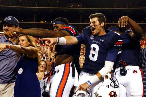 Auburn quarterback Jarrett Stidham (8) and Auburn wide receiver Kyle Davis (11) celebrate with fans after defeating Mississippi State 49-10 in an NCAA college football game, Saturday, Sept. 30, 2017, in Auburn, Ala.