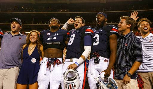 Auburn quarterback Jarrett Stidham (8), wide receiver Kyle Davis (11), and wide receiver Nate Craig-Myers (3) celebrate with fans after defeating Mississippi State 49-10 in an NCAA college football game, Saturday, Sept. 30, 2017, in Auburn, Ala.