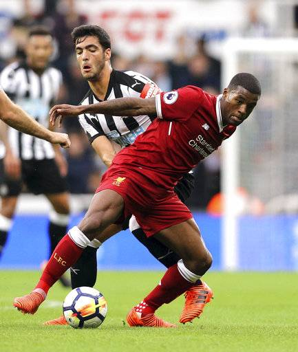 Newcastle United's Mikel Merino and Liverpool's Georginio Wijnaldum, right, battle for the ball during the English Premier League soccer match at St James' Park, Newcastle, England, Sunday, Oct. 1, 2017. (Owen Humphreys/PA via AP)