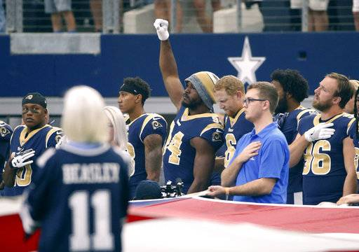Los Angeles Rams linebacker Robert Quinn (94) raises his fist during the playing of the national anthem before an NFL football game against the Dallas Cowboys, Sunday, Oct. 1, 2017, in Arlington, Texas.