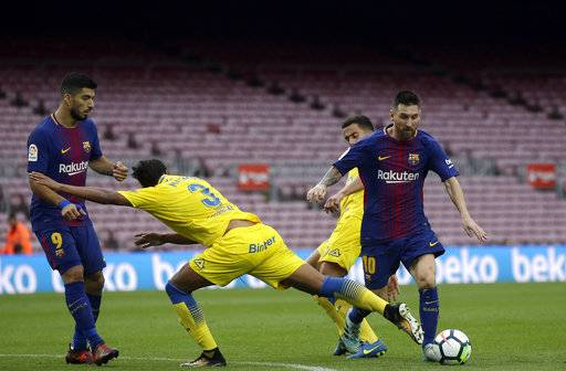 Barcelona's Lionel Messi, right, is challenged by Las Palmas' Mauricio Lemos, center, during the Spanish La Liga soccer match between Barcelona and Las Palmas at the Camp Nou stadium in Barcelona, Spain, Sunday, Oct. 1, 2017. Barcelona's Spanish league game against Las Palmas is played without fans amid the controversial referendum on Catalonia's independence.