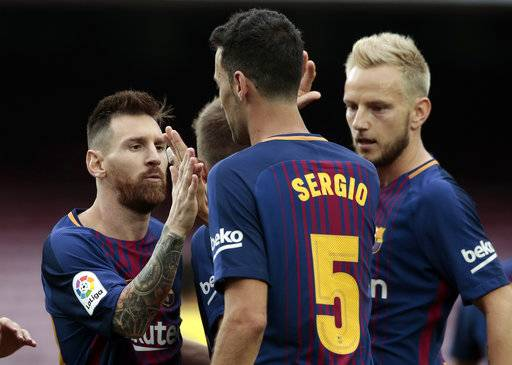 Barcelona's Lionel Messi, left, celebrates a goal with Barcelona's Sergio, center, during the Spanish La Liga soccer match between Barcelona and Las Palmas at the Camp Nou stadium in Barcelona, Spain, Sunday, Oct. 1, 2017. Barcelona's Spanish league game against Las Palmas is played without fans amid the controversial referendum on Catalonia's independence.