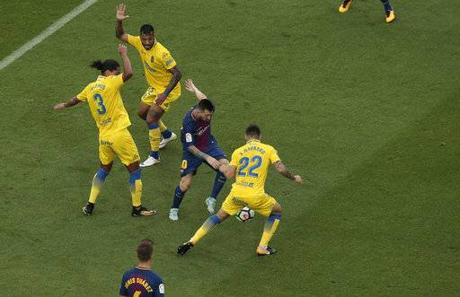 Barcelona's Lionel Messi, center, is challenged by Las Palmas' Ximo Navarro during the Spanish La Liga soccer match between Barcelona and Las Palmas at the Camp Nou stadium in Barcelona, Spain, Sunday, Oct. 1, 2017. Barcelona's Spanish league game against Las Palmas is played without fans amid the controversial referendum on Catalonia's independence.