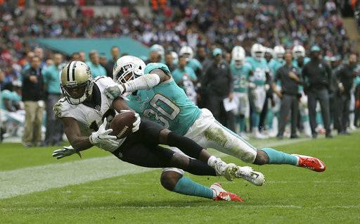 New Orleans Saints wide receiver Michael Thomas, left, scores a touchdown against Miami Dolphins cornerback Cordrea Tankersley (30) during the second half of an NFL football game at Wembley Stadium in London, Sunday Oct. 1, 2017.