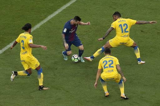 Barcelona's Lionel Messi, center, is challenged by Las Palmas' Michel Macedo during the Spanish La Liga soccer match between Barcelona and Las Palmas at the Camp Nou stadium in Barcelona, Spain, Sunday, Oct. 1, 2017. Barcelona's Spanish league game against Las Palmas is played without fans amid the controversial referendum on Catalonia's independence.