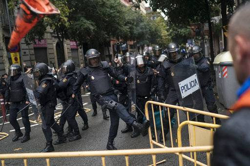 Spanish riot police removes fences thrown by people to them as they try to prevent people from reaching a voting site at a school assigned to be a polling station by the Catalan government in Barcelona, Spain, Sunday, 1 Oct. 2017. Catalan pro-referendum supporters vowed Saturday to ignore a police ultimatum to leave the schools they are occupying to use in a vote seeking independence from Spain.