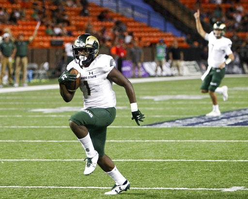 As Colorado State quarterback Nick Stevens (7) reacts in the background, wide receiver Michael Gallup (4) runs the ball in for a third quarter touchdown against Hawaii at the NCAA college football game, Saturday, Sept. 30, 2017, in Honolulu.