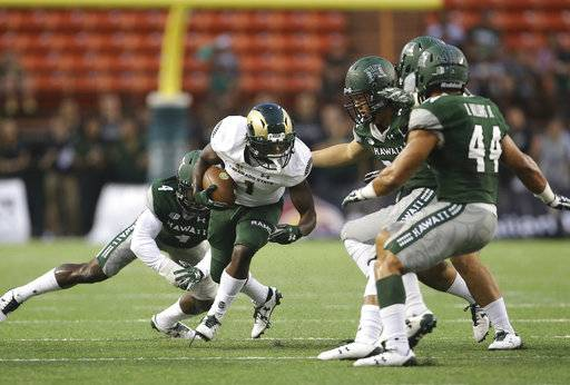 Colorado State running back Dalyn Dawkins (1) tries to break through the Hawaii defense during the first quarter of the NCAA college football game, Saturday, Sept. 30, 2017, in Honolulu.