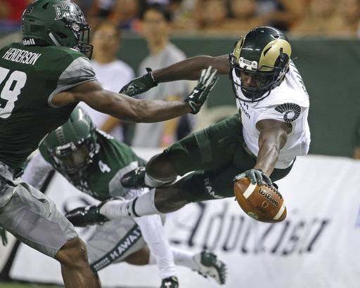 While guarded by Hawaii defensive backs Trayvon Henderson (39) and Daniel Lewis Jr. (4), Colorado State wide receiver Michael Gallup (4) tries to leap into the end zone but stepped out of bounds during the second quarter of the NCAA college football game against Hawaii, Saturday, Sept. 30, 2017, in Honolulu.