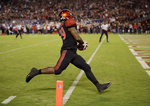 San Diego State kick returner Juwan Washington runs back the opening kickoff for a touchdown during the first half of an NCAA college football game against Northern Illinois Saturday, Sept. 30, 2017, in San Diego.