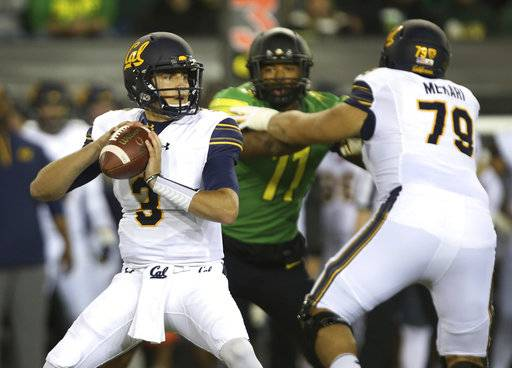 California quarterback Ross Bowers, left, looks down field under pressure from Oregon's Justin Hollins as he battles California's Patrick Mekari, right, during the first quarter of an NCAA college football game Saturday, Sept. 230, 2017, in Eugene, Ore.
