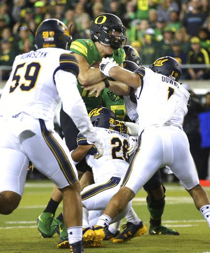 Oregon's Justin Herbert, center, drives into the end zone for a touchdown against California's Quentin Tartabull, bottom, and Devante Downs during the first quarter of an NCAA college football game Saturday, Sept. 30, 2017, in Eugene, Ore.