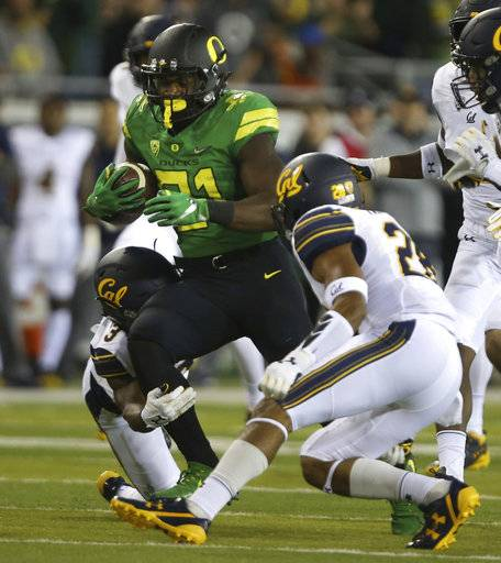 Oregon's Royce Freeman, center, rushes against California's Elijah Hicks, left, and Quentin Tartabull, right, during the first quarter of an NCAA college football game Saturday, Sept. 230, 2017, in Eugene, Ore.