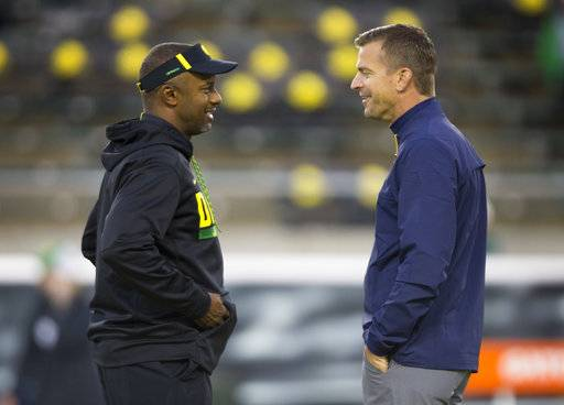 Oregon head coach Willie Taggart, left, talks with California head coach Justin Wilcox before their NCAA college football game Saturday, Sept. 30, 2017, in Eugene, Ore.