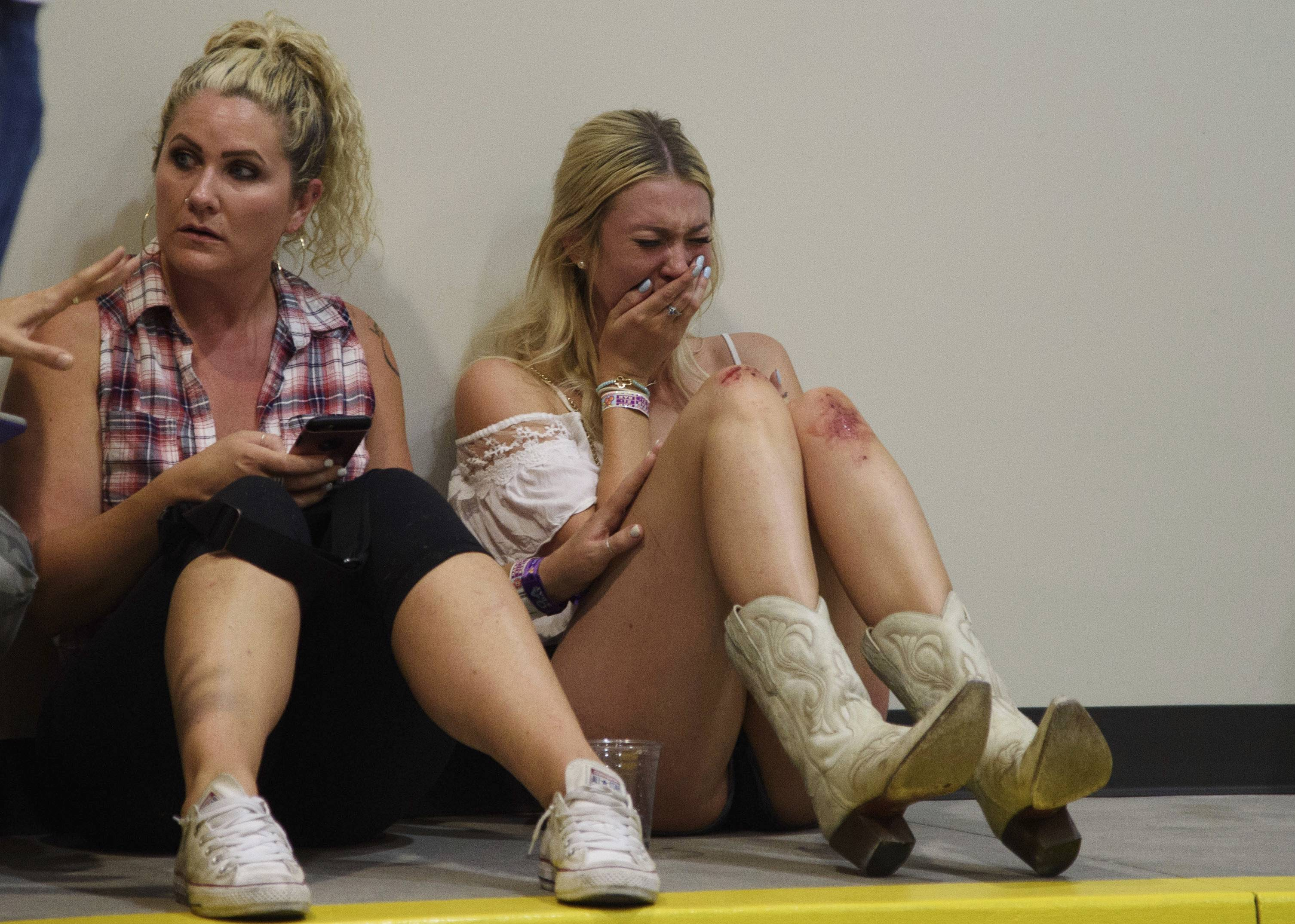 A woman cries while hiding inside the Sands Corporation plane hangar after a mass shooting in which dozens were killed at the Route 91 Harvest Festival on Sunday, Oct. 1, 2017, in Las Vegas.