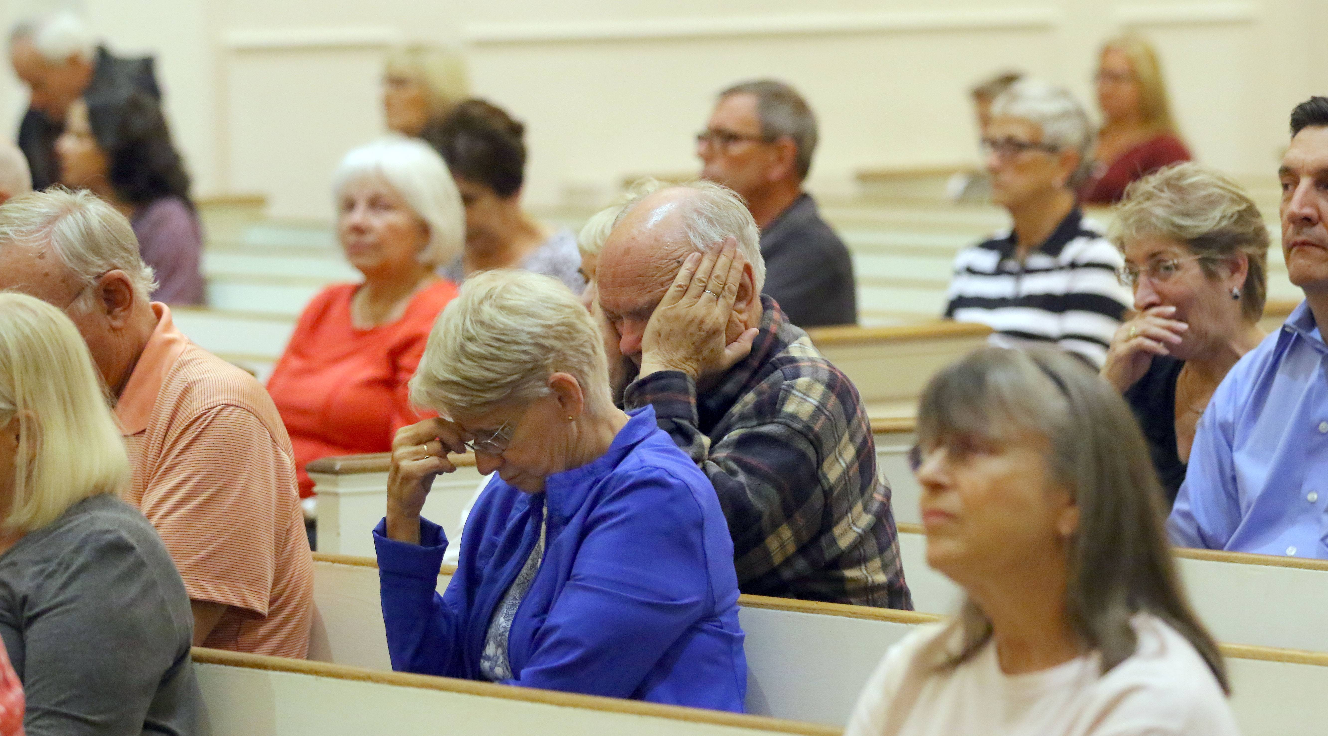 Parishioners pray during a service for the Las Vegas shooting victims Monday evening at St. James Catholic Church in Arlington Heights.