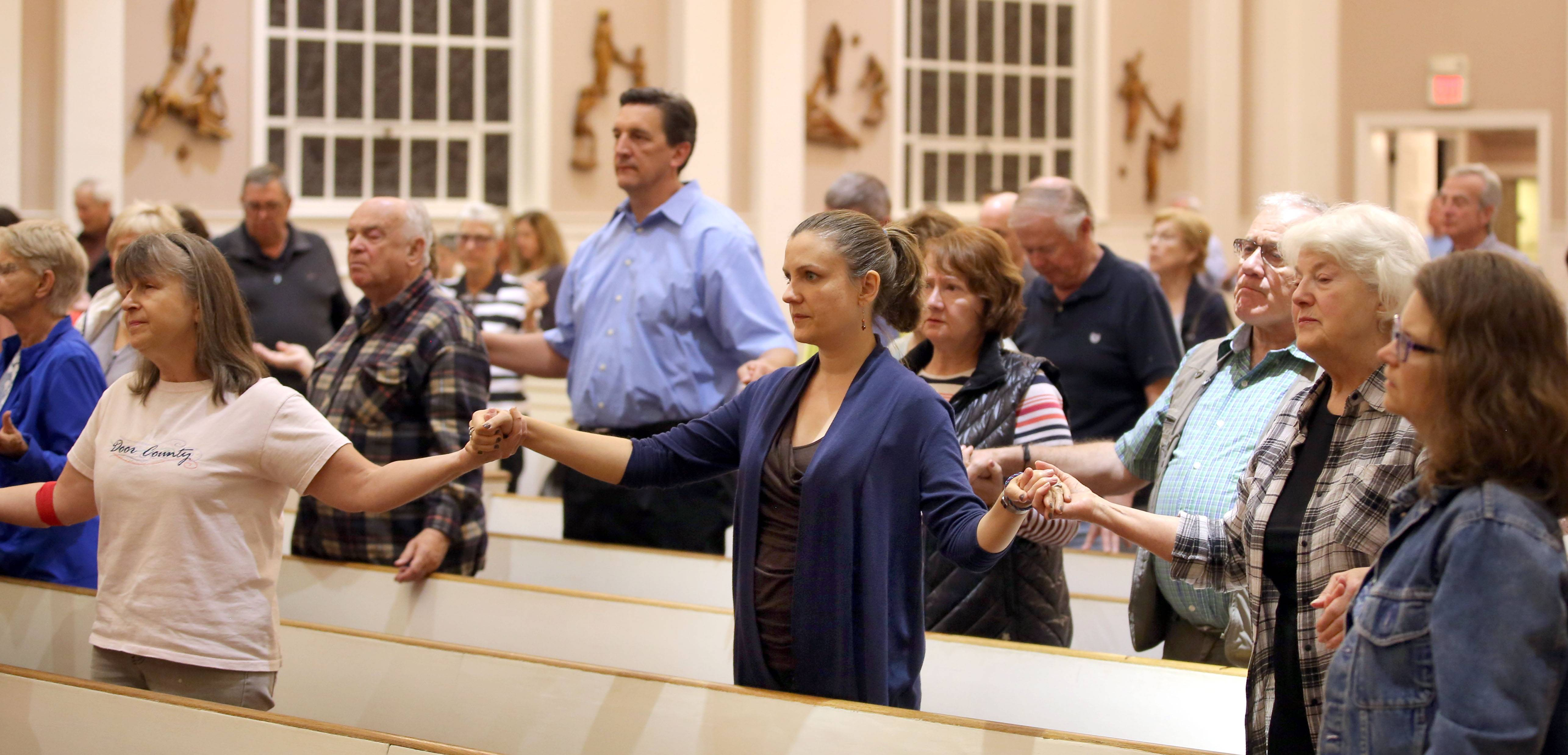 Parishioners of St. James Catholic Church in Arlington Heights hold hands during a prayer vigil for the Las Vegas shooting victims Monday evening.