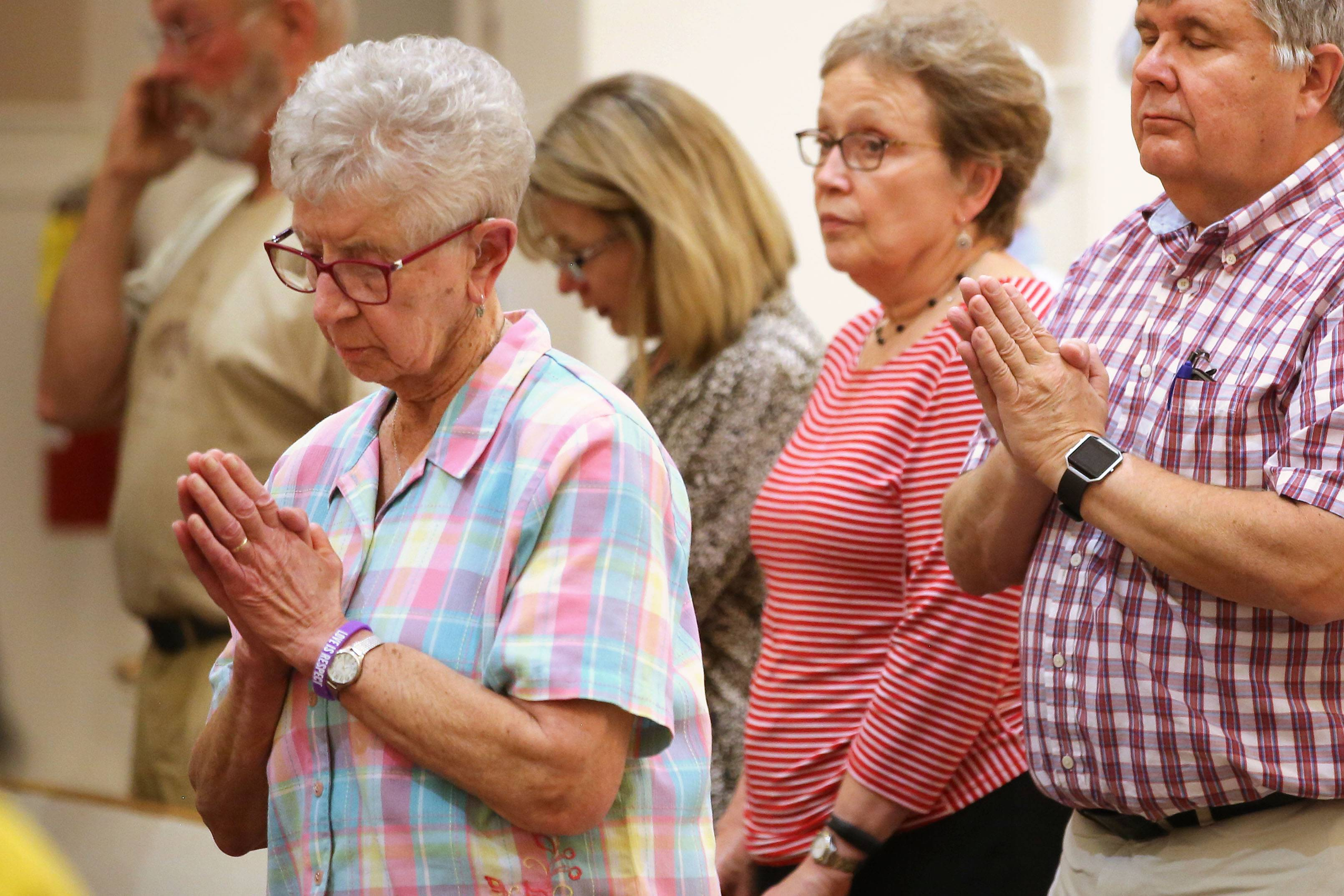 Sister Joanne Grib, left, of Arlington Heights prays during a prayer vigil for the Las Vegas shooting victims Monday evening at St. James Catholic Church in the village.