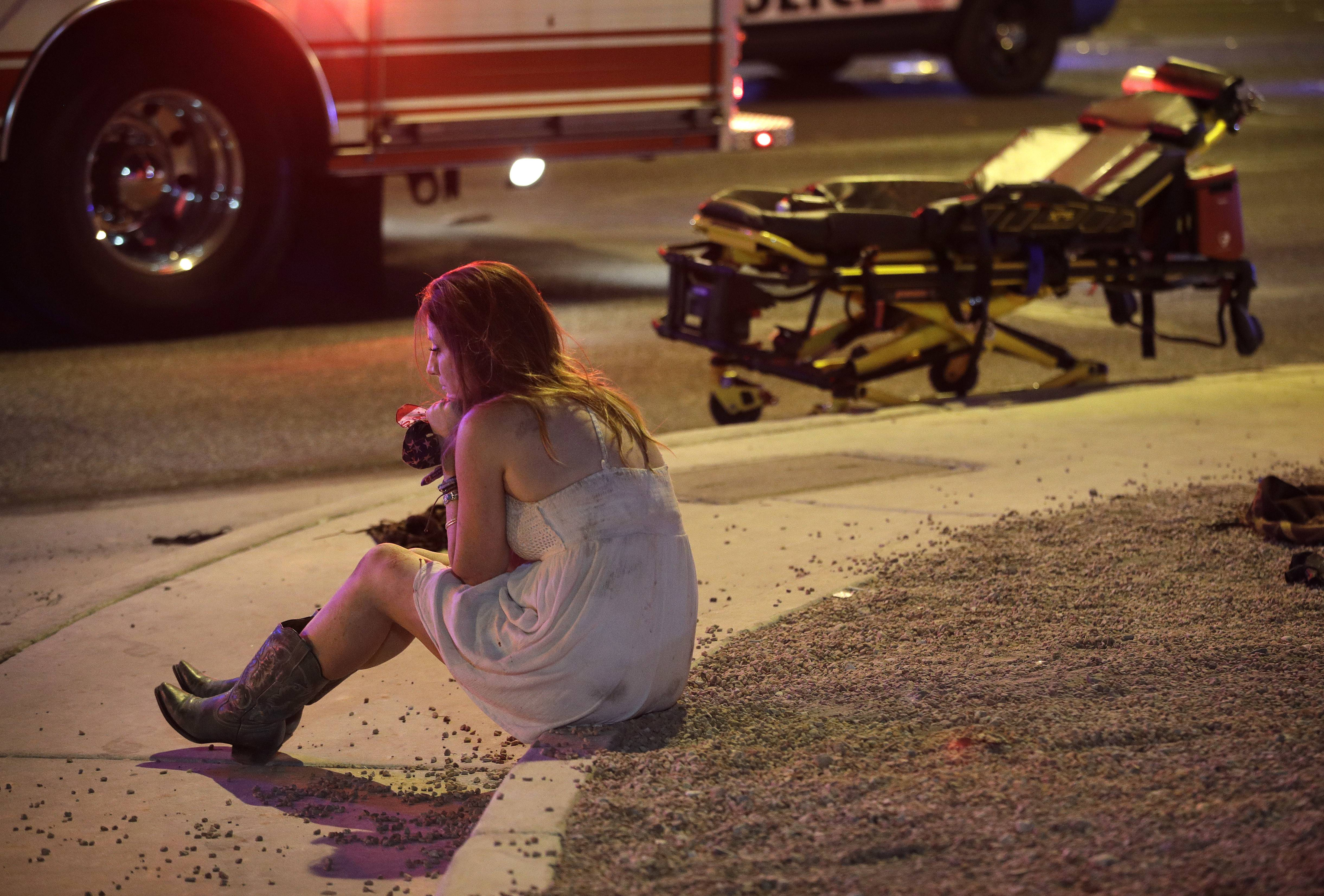 A woman sits on a curb at the scene of a shooting outside of a music festival along the Las Vegas Strip, Monday, Oct. 2, in Las Vegas. Multiple victims were being transported to hospitals after the shooting late Sunday.