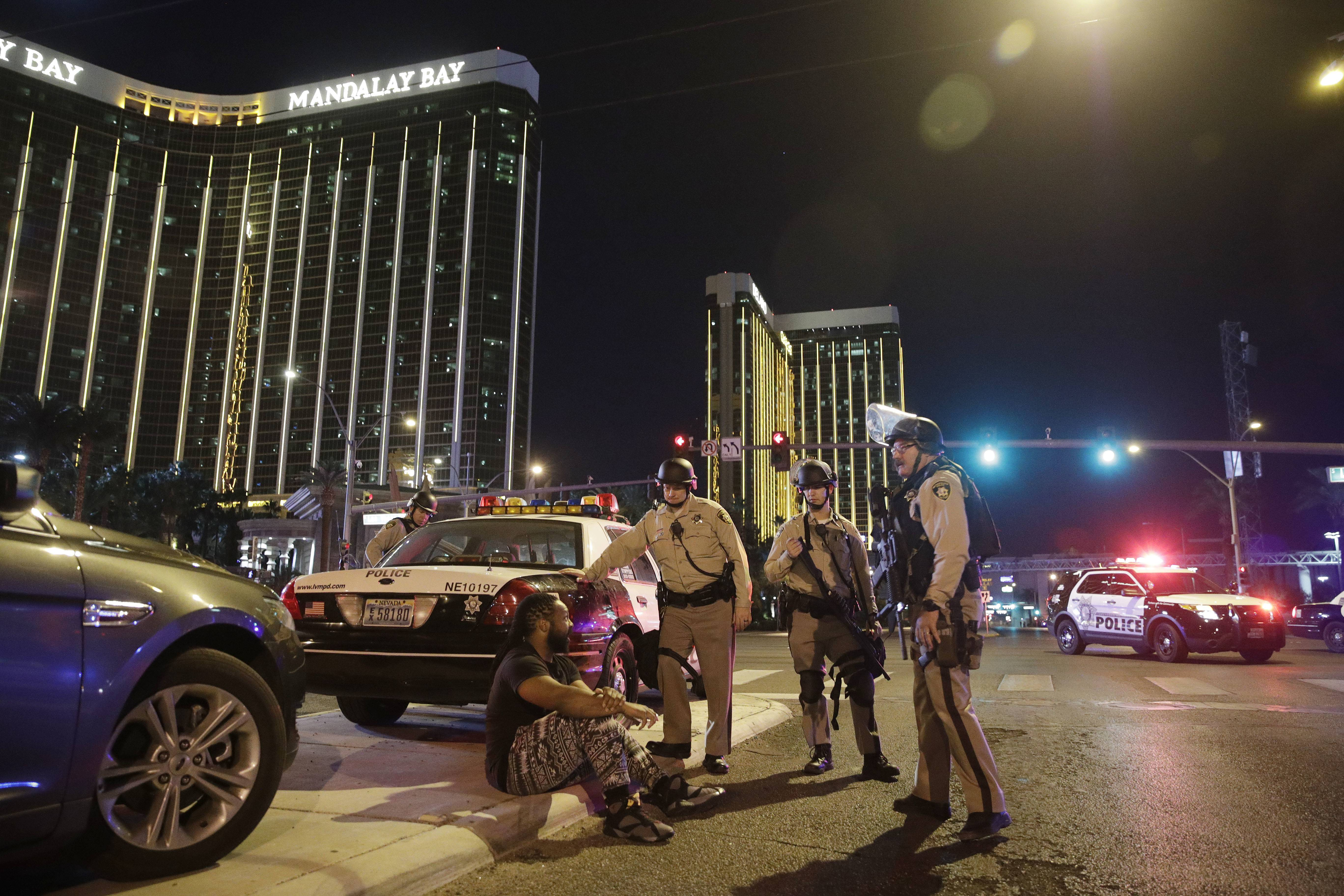 Police officers stand at the scene of a shooting near the Mandalay Bay resort and casino on the Las Vegas Strip, Sunday, Oct. 1, 2017, in Las Vegas. Multiple victims were being transported to hospitals after a shooting late Sunday at a music festival on the Las Vegas Strip.
