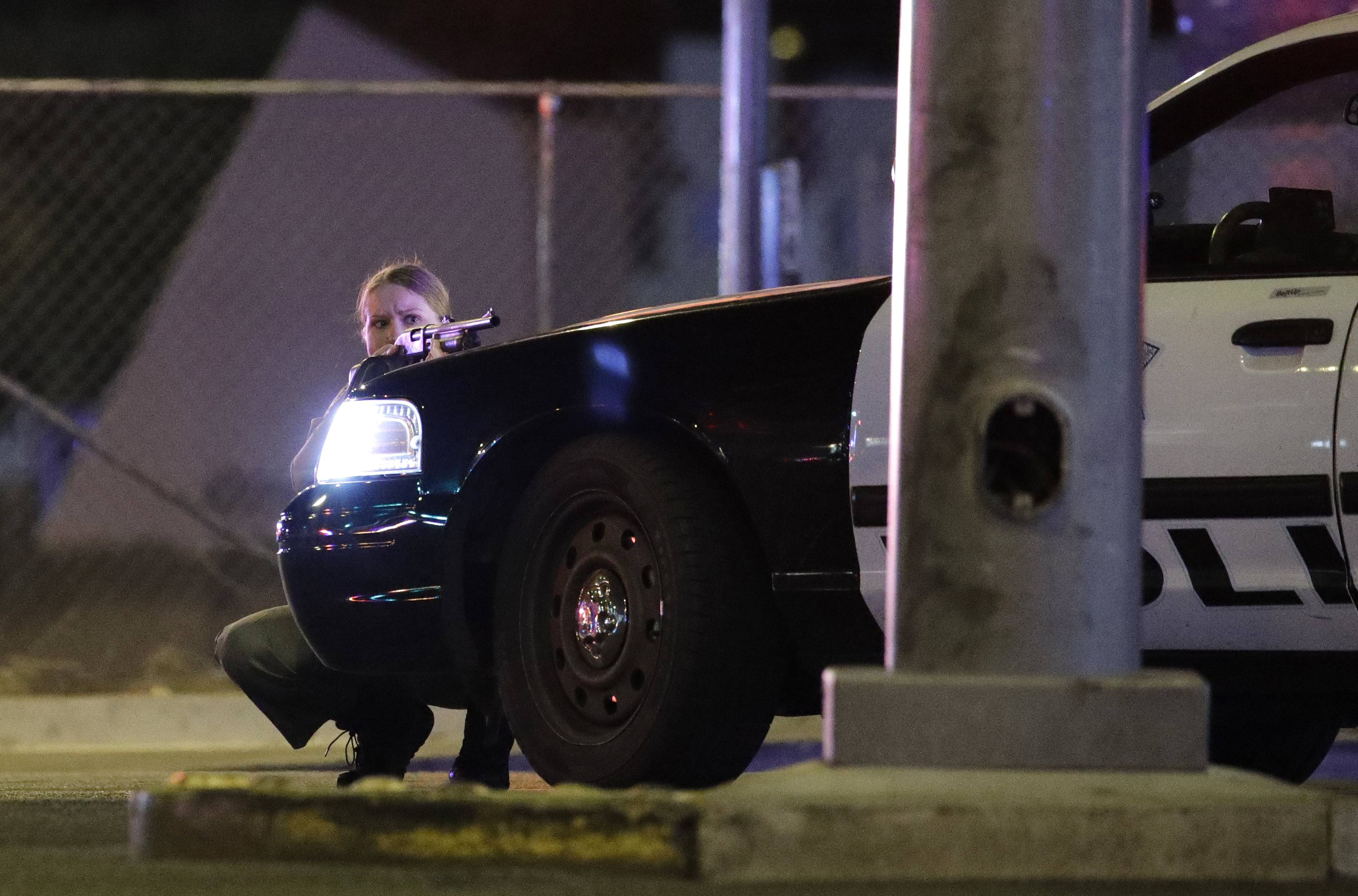 A police officer takes cover behind a police vehicle during a shooting near the Mandalay Bay resort and casino on the Las Vegas Strip, Sunday, Oct. 1, 2017, in Las Vegas.