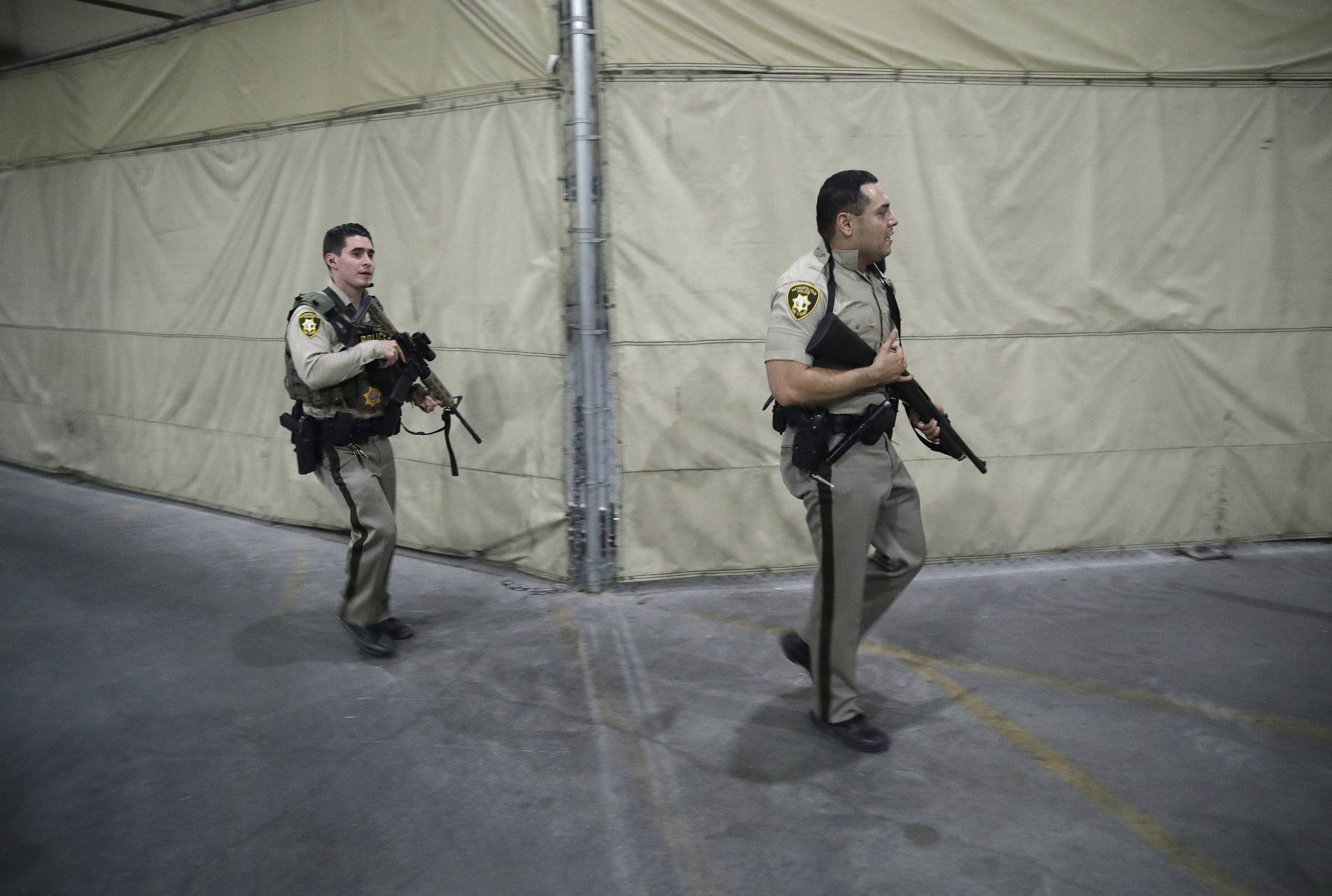 Police officers enter the Mandalay Bay resort and casino during a shooting near the Mandalay Bay resort and casino on the Las Vegas Strip, Sunday, Oct. 1, 2017, in Las Vegas.