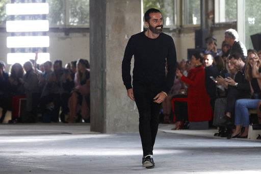 Italian fashion designer Giambattista Valli accepts applauses after his Spring-Summer 2018 ready-to-wear fashion collection presented Monday, Oct. 2, 2017 in Paris.