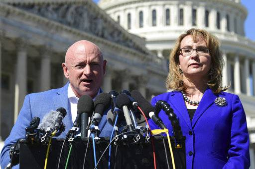 Former Rep. Gabrielle Giffords, D-Ariz., right, listens as her husband Mark Kelly, left, speaks on Capitol Hill in Washington, Monday, Oct. 2, 2017, about the mass shooting in Las Vegas. Giffords, was a congresswoman when she was shot in an assassination attempt in 2011.
