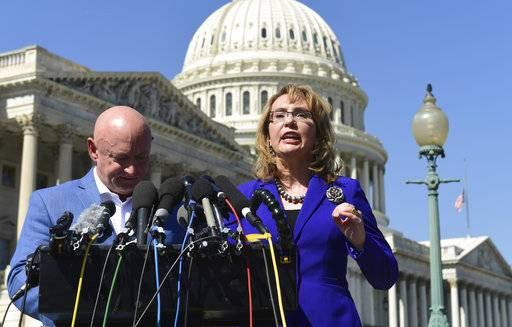 Former Rep. Gabrielle Giffords, D-Ariz., right, standing with her husband Mark Kelly, left, speaks on Capitol Hill in Washington, Monday, Oct. 2, 2017, about the mass shooting in Las Vegas. Giffords, was a congresswoman when she was shot in an assassination attempt in 2011.