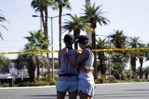Two women embrace in front of the concert venue where a mass shooting took place on the Las Vegas Strip, Monday, Oct. 2, 2017, in Las Vegas.