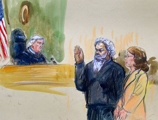 FILE - This June 28, 2014, file courtroom sketch, United States Magistrate, Judge John Facciola, swearing in the defendant, Libyan militant Ahmed Abu Khattala, wearing a headphone, as his attorney Michelle Peterson watches during a hearing at the federal U.S. District Court in Washington. The trial of Khattala, the Libyan militant accused of being the mastermind of the 2012 Benghazi attacks is scheduled to begin on Oct. 2, 2017. (Dana Verkouteren via AP, File)