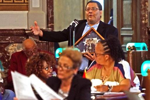 "Alderman Joseph Vaccaro, Ward 23, speaks at a Board of Aldermen meeting in St. Louis on Friday, Sept. 29, 2017. Vaccaro introduced a resolution recognizing police for their efforts to keep the city safe during recent unrest. ""There are two sides to every story, "" he said on the floor of the board's chambers, clutching a photo of an officer killed in the line of duty. (Laurie Skrivan/St. Louis Post-Dispatch via AP)"