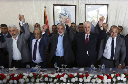 From left to right in front row, Hamas leader in the Gaza Strip Yahya Sinwar, Head of Palestinian General Intelligence Majid Faraj, Head of the Hamas political bureau Ismail Haniyeh, Palestinian Prime Minister Rami Hamdallah and an Egyptian mediator hold their hands up during a meeting in Gaza City, Monday, Oct. 2, 2017. Hamdallah is in Gaza for the most ambitious attempt yet to end the 10-year rift between rival Palestinian factions Fatah and Hamas.