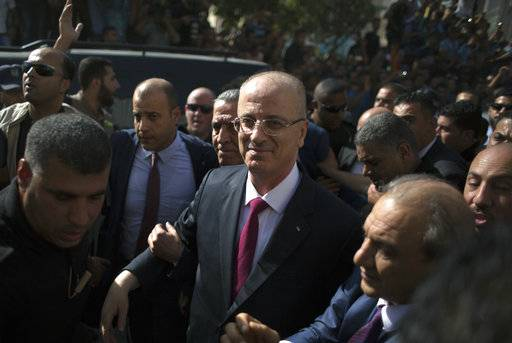 Palestinian Prime Minister Rami Hamdallah is surrounded by security during his visit to the Shejaiya neighborhood in Gaza City, Monday, Oct. 2, 2017. Hamdallah is in Gaza for the most ambitious attempt yet to end the 10-year rift between rival Palestinian factions Fatah and Hamas.