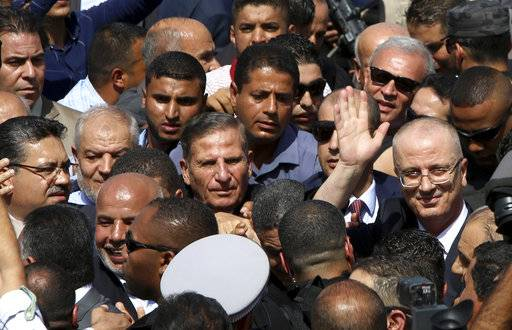 Palestinian Prime Minister Rami Hamdallah, greets his supporters on his arrival to the Palestinian side of the Beit Hanoun border crossing in the northern Gaza Strip, Monday, Oct. 2, 2017. Hamdallah is in Gaza for the most ambitious attempt yet to end the 10-year rift between rival Palestinian factions Fatah and Hamas.