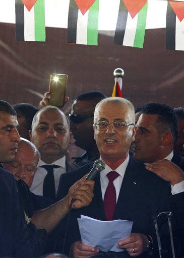 Palestinian Prime Minister Rami Hamdallah, gives a press conference on his arrival to the Palestinian side of the Beit Hanoun border crossing in the northern Gaza Strip, Monday, Oct. 2, 2017. Hamdallah is in Gaza for the most ambitious attempt yet to end the 10-year rift between rival Palestinian factions Fatah and Hamas.