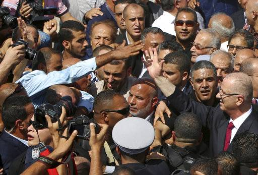 Palestinian Prime Minister Rami Hamdallah, reaches out to shake hands with a supporter on his arrival to the Palestinian side of the Beit Hanoun border crossing in the northern Gaza Strip, Monday, Oct. 2, 2017. Hamdallah is in Gaza for the most ambitious attempt yet to end the 10-year rift between rival Palestinian factions Fatah and Hamas.
