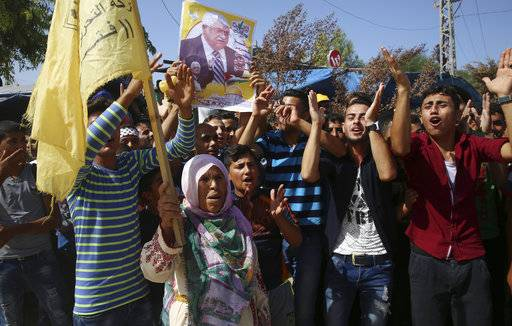 Fatah supporters chant slogans while other carry a picture of Palestinian president Mahmoud Abbas, while waiting for the Prime Minister Rami Hamdallah, at the Palestinian side of the Beit Hanoun border crossing in the northern Gaza Strip, Monday, Oct. 2, 2017. Hamdallah is in Gaza for the most ambitious attempt yet to end the 10-year rift between rival Palestinian factions Fatah and Hamas.