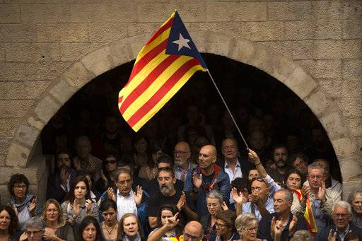 "Catalan independence supporters, one waving an ""estelada"", or Catalonia independence flag, applaud during a rally outside the city hall of Girona, Spain, Monday, Oct. 2, 2017. Spanish riot police smashed their way into polling stations to try to halt a disputed independence referendum in Catalonia on Sunday and fired rubber bullets at protesters outside a Barcelona polling station, with Catalan officials saying more than 330 people were injured, some seriously."