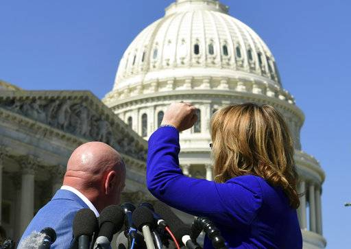 "Former Rep. Gabrielle Giffords, D-Ariz., right, shakes her fist at the United States Capitol as she and her husband Mark Kelly, left, speak on Capitol Hill in Washington, Monday, Oct. 2, 2017, about the mass shooting in Las Vegas. Giffords raised her fist at the Capitol and said ""the nation is counting on you� after the deadly mass shooting in Las Vegas."