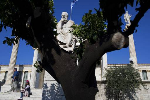 The marble statue of ancient Greek philosophers Socrates, stands in front of the Athens Academy as a Greek flag flies, on Monday, Oct. 2, 2017 . Greece's government on Monday presented what it calls the last of the bailout-era state budgets, predicting economic growth of 2.4 percent and a significant budget surplus in 2018. In the draft 2018 budget, the economy is expected to expand 1.8 percent this year, up from no growth last year.