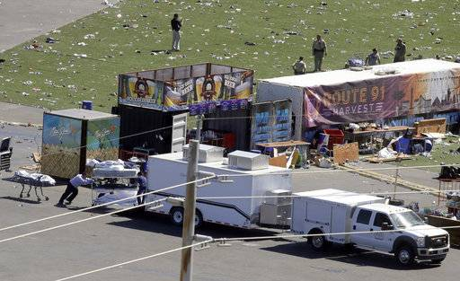 Investigators loads a truck with bodies from the scene of a mass shooting at a music festival near the Mandalay Bay resort and casino on the Las Vegas Strip Monday, Oct. 2, 2017, in Las Vegas.