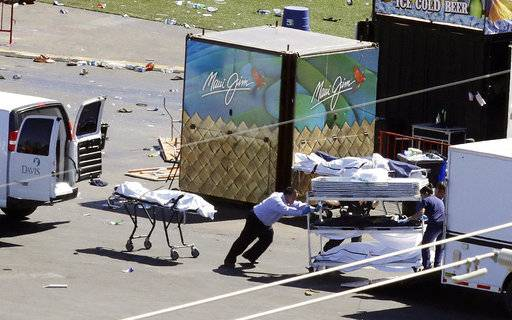 Investigators load bodies from the scene of a mass shooting at a music festival near the Mandalay Bay resort and casino on the Las Vegas Strip on Monday, Oct. 2, 2017, in Las Vegas.