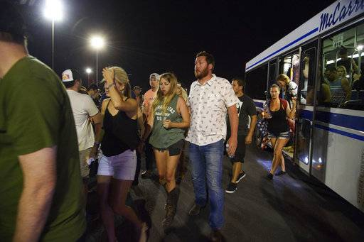 People arrive to Thomas & Mack Center via bus after hiding inside the Sands Corporation plane hangar after a mass shooting in which dozens were killed at the Route 91 Harvest country festival on early Monday, Oct. 2, 2017, in Las Vegas. (Al Powers/Invision/AP)