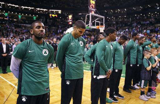 Boston Celtics guard Kyrie Irving, left, and his teammates pause for a moment of silence for victims of the Las Vegas concert shooting, prior to the team's NBA preseason basketball game against the Charlotte Hornets in Boston, Monday, Oct. 2, 2017.
