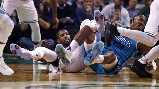 Boston Celtics guard Kyrie Irving, left, and Charlotte Hornets center Dwight Howard, right, become  entangled while chasing a loose ball during the first quarter of an NBA preseason basketball game in Boston, Monday, Oct. 2, 2017.