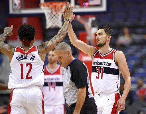 Washington Wizards guard Tomas Satoransky (31), of the Czech Republic, high-fives Kelly Oubre Jr. (12) during the second half of an NBA basketball exhibition game, Monday, Oct. 2, 2017, in Washington.